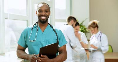 Smiling African doctor in scrubs